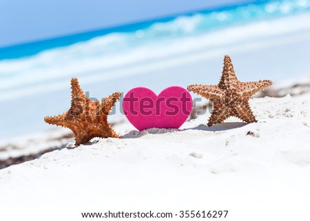 Red sweet heart shape with two starfishes on white sandy beach with sea background. Happy Valentines Day at summertime on exotic vacations.