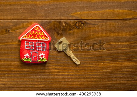 Red sweet  house and key on wooden background - stock photo