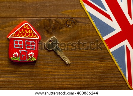 Red sweet  house , key and british flag on wooden background - stock photo
