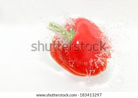 Red sweet pepper falling into the water
