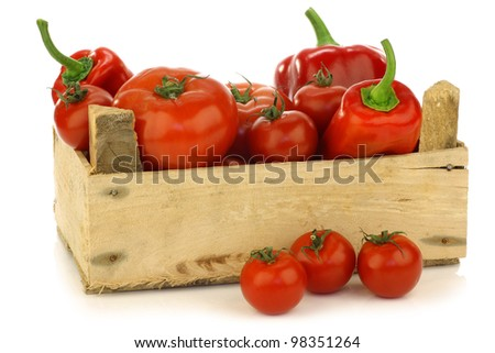 red sweet peppers and tomatoes in a wooden crate on a white background