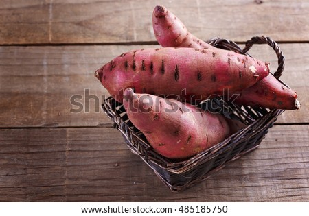 Red Sweet potato in a woven basket over rustic wooden background closeup