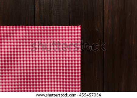red tablecloth on dark wooden background