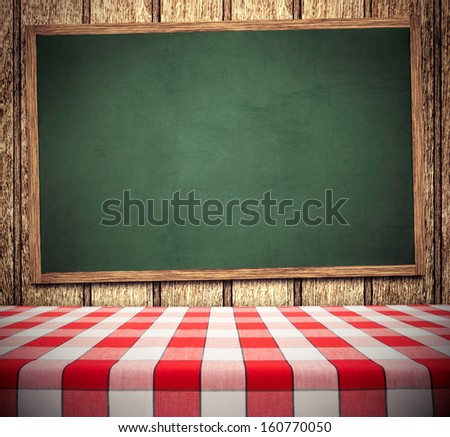Red tablecloth on green chalkboard, copy space for menu - stock photo