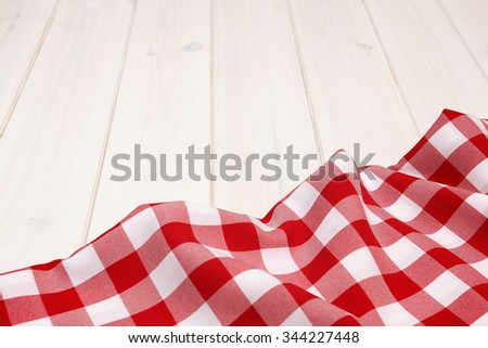 Red tablecloth on wooden boards background - stock photo