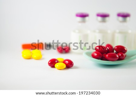 Red tablet in spoon on medicine vials background - stock photo
