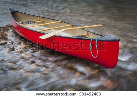red tandem canoe with a paddle on a shallow rocky river