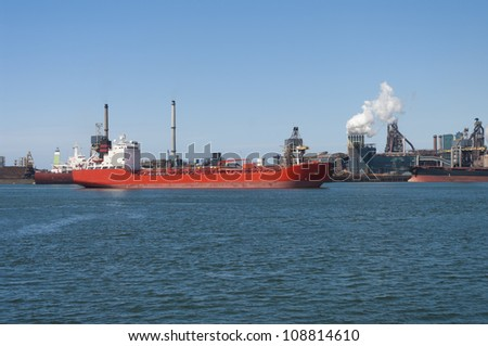 red tanker passing by a large steel factory in IJmuiden, Netherlands - stock photo
