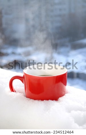 Red Tea Cup In Snow in Morning Winter Mood Christmas - stock photo