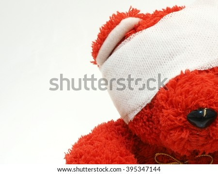 Red teddy bear with bandage over his head with free text space on left - stock photo