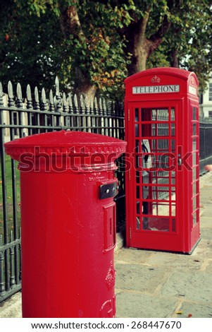 Red telephone and post box in street with historical architecture in London. - stock photo
