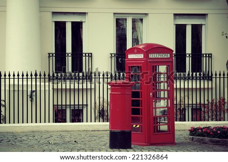 Red telephone booth and mail box in street in London as the famous icons. - stock photo