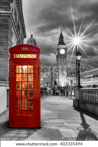 Red telephone booth in front of the Big Ben in London, United Kingdom, by night - stock photo
