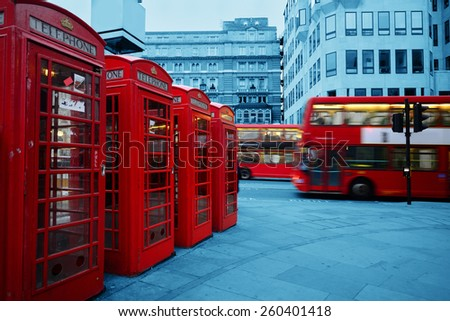 Red telephone box and bus in street with historical architecture in London. - stock photo
