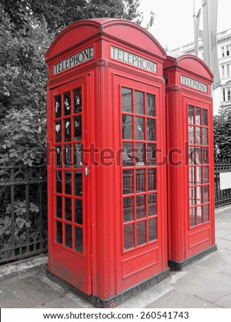 Red telephone box in London over desaturated black and white background
