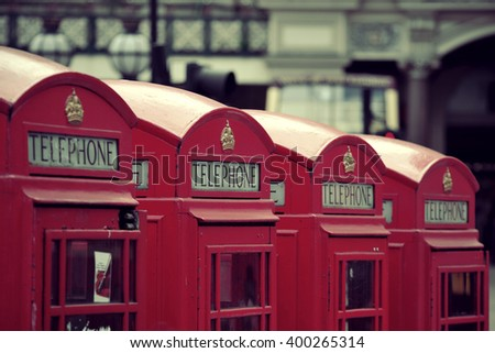 Red telephone box in street with historical architecture in London. - stock photo