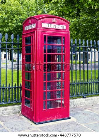 Red telephone box; UK British telephone box or kiosk on street against park railings  - stock photo