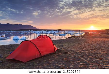 Red tent during a beautiful sunrise at the Jokulsarlon lake - Trekking on Iceland. - stock photo