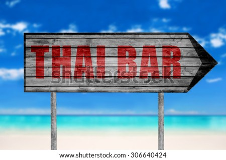 Red Thai Bar wooden sign with on a beach background - stock photo