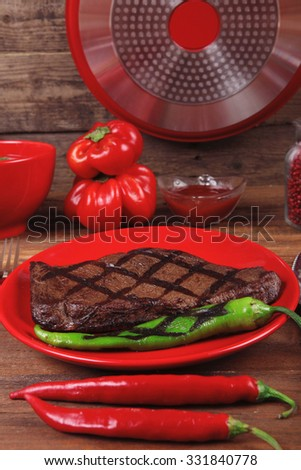 red theme lunch : fresh grilled bbq roast beef steak red plate green chili tomato soup ketchup sauce paprika small jug glass ground pepper american peppercorn and modern cutlery served on wooden table - stock photo