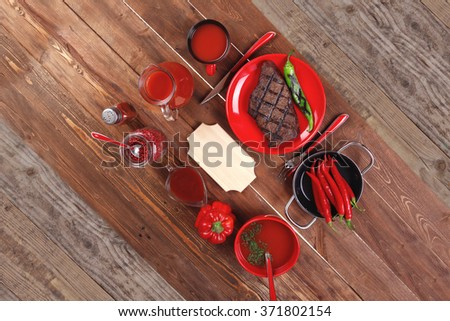 red theme lunch : fresh grilled bbq roast beef steak red plate green chili tomato soup ketchup sauce paprika small glass pepper american peppercorn modern cutlery served wooden table empty nameplate - stock photo