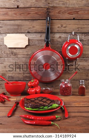 red theme lunch : fresh grilled bbq roast beef steak red plate green chili tomato soup sauce small jug glass ground pepper american peppercorn modern cutlery served wooden table with empty nameplate - stock photo