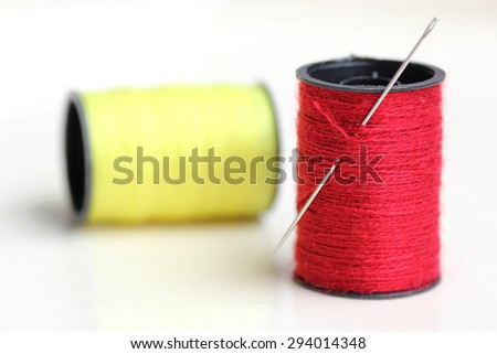 Red thread and needle in isolated - stock photo