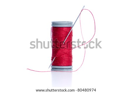 Red thread bobbin and needle on white background. - stock photo
