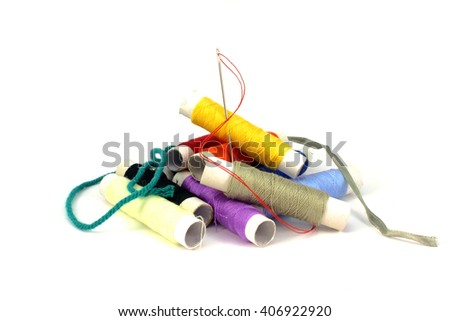 Red thread in the needle in a pile of colorful yarn - stock photo
