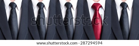 Red tie between black neckties as stand out of the pattern or crowd concept - stock photo
