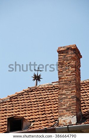 red tile roof with brick chimney and metal vane closeup on blue sky background - stock photo