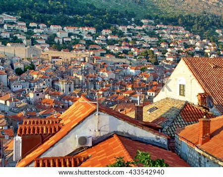 Red tile roofs of the Old Town, Dubrovnik, Croatia, seen from above, with the suburbs on a hill in the distance outside the walled city - stock photo