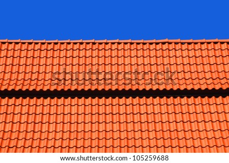 Red tiles roof and blue sky background - stock photo