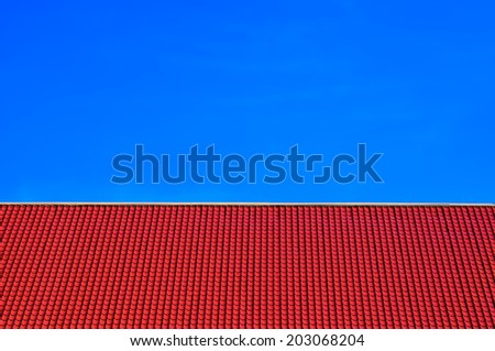 Red tiles roof on clear blue sky background - stock photo