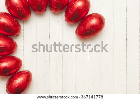 red tinfoil wrapped chocolate easter eggs on white wood table - stock photo