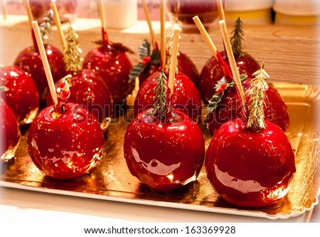 Red toffee love apple decorated with Santa Claus and Christmas tree. Christmas market in Paris. Bleached angles. - stock photo