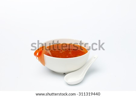 Red tomato cream soup in white ceramic cup isolated on white background. - stock photo