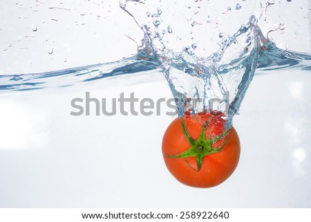 red tomato dropped into blue water on white - stock photo