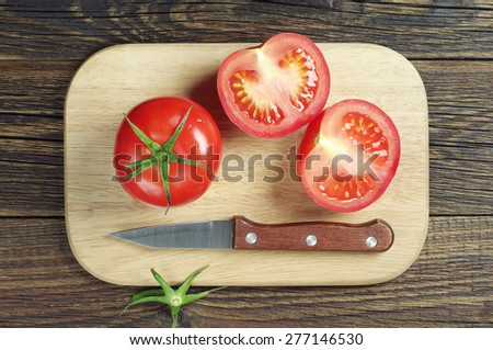 Red tomato slices and knife on cutting board, top view - stock photo