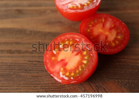 Red tomato slices on wooden background