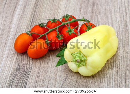 Red tomatoes on the branch with yellow pepper