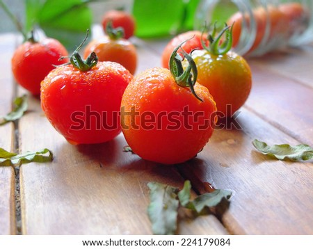 Red tomatoes on wooden table. - stock photo