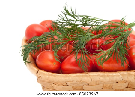 Red tomatoes with fennel in a wattled basket on a white background - stock photo