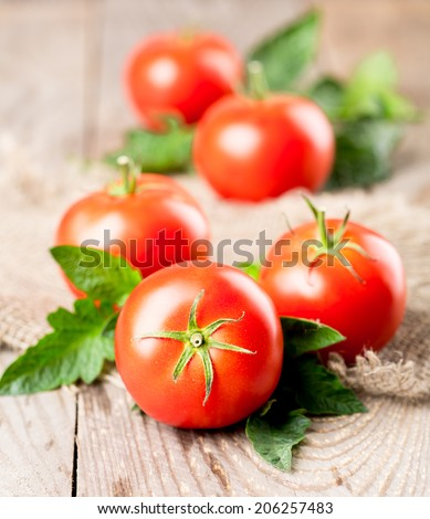 red tomatoes with leaves on a wooden table