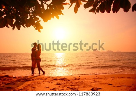 Red toned picture of a couple on a tropical beach at sunset