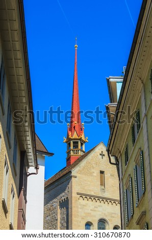 Red top of famous church between buildings and blue sky in downtown Zurich, Switzerland.