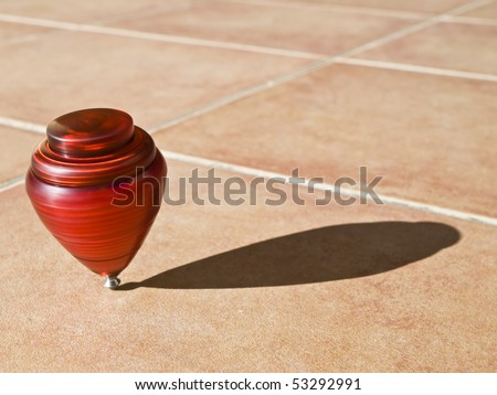 Red top spinning on its axis, with the sun casting its shadow on the pavement - stock photo