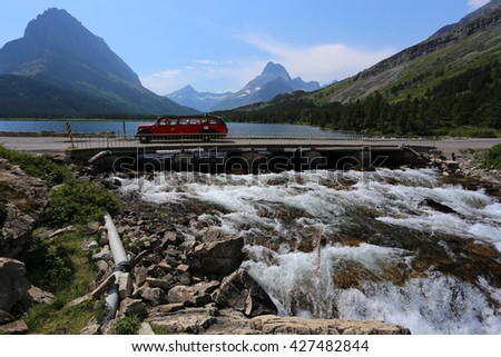Red Tour Bus Swiftcurrent Lake Glacier National Park waterfall - stock photo