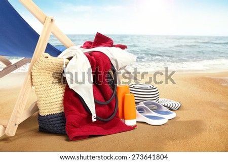 red towel hat and bag with blue chair on sand