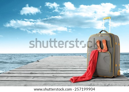 red towel suitcase and gray pier  - stock photo